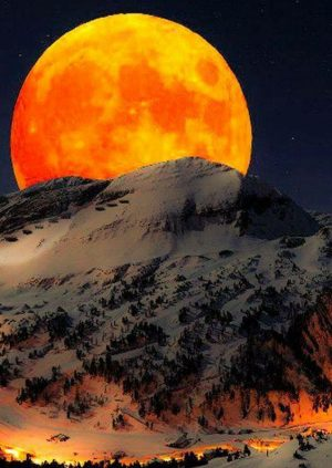 A Large Moon Rising over the Pristine Mountain Tops of Snow