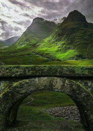 A Green Ancient Stone Bridge Passing Though a Mountain Way